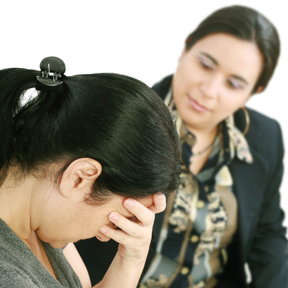 A visibly upset woman talking with a counselor