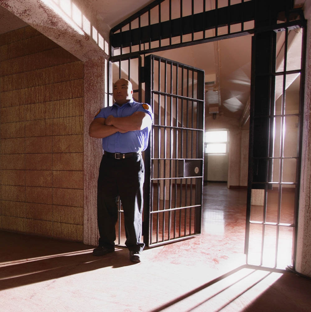 A male corrections officer standing in front of an open cell