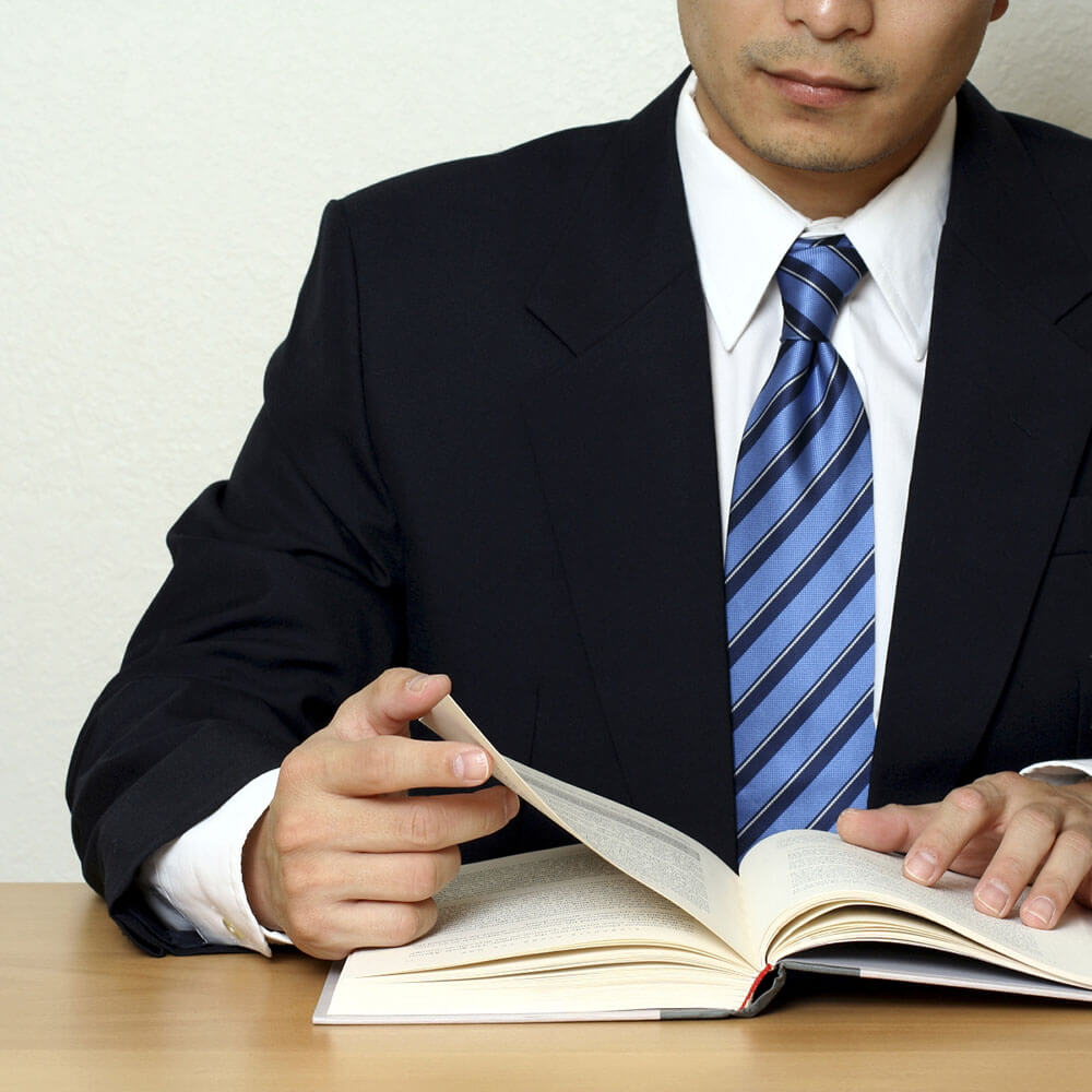 A man in a suit and tie reading a book