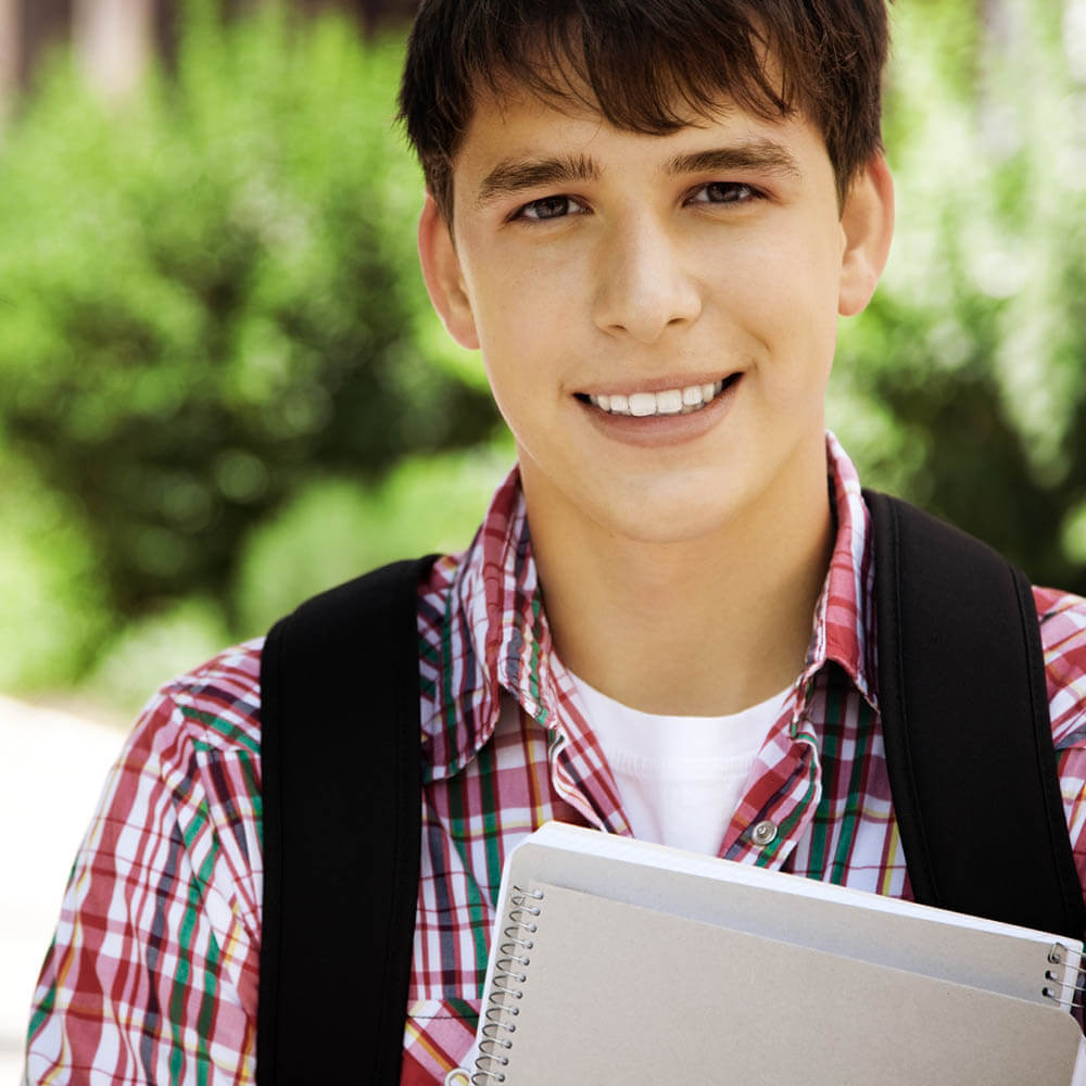 A male student holding notebooks