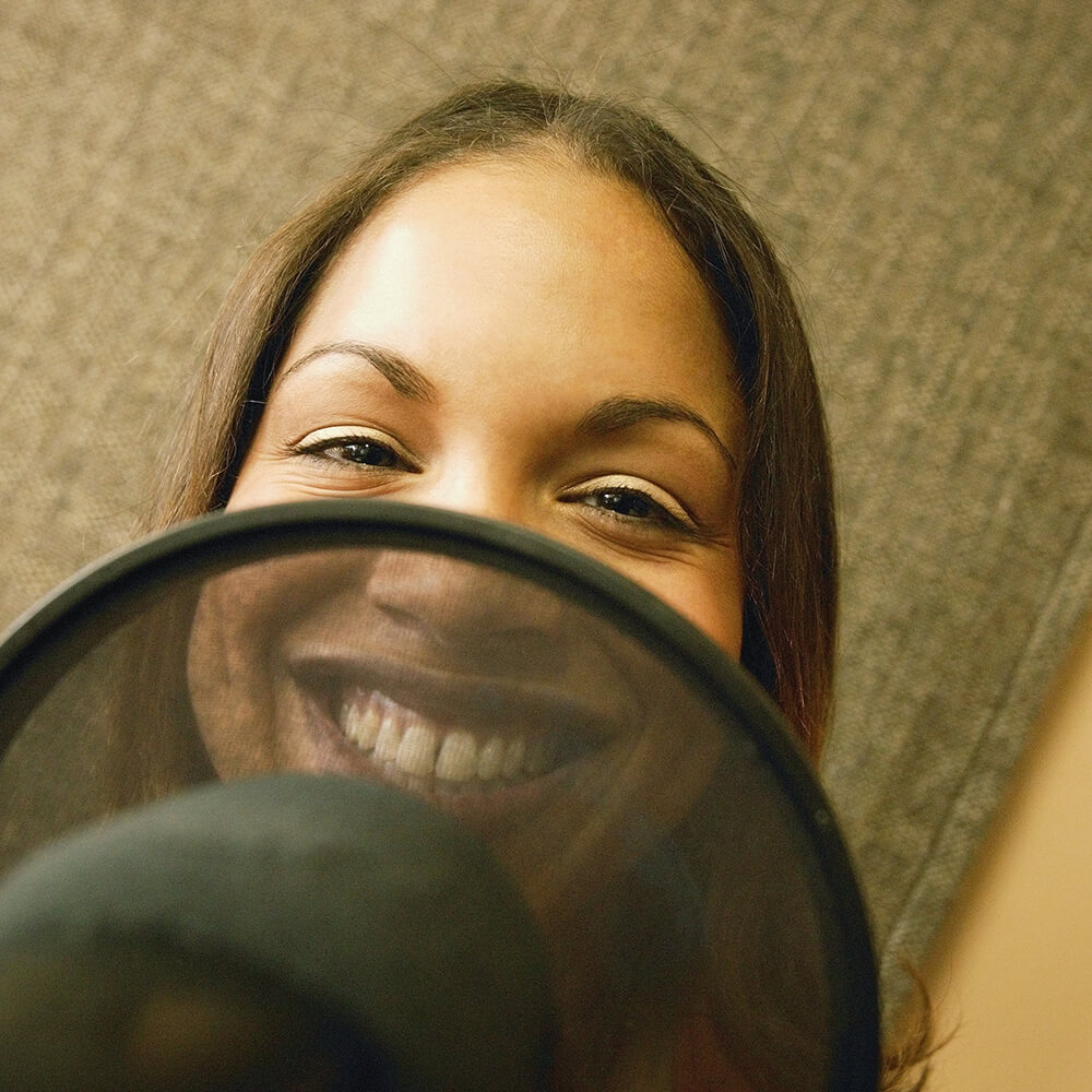 A female smiling behind a microphone in a recording booth