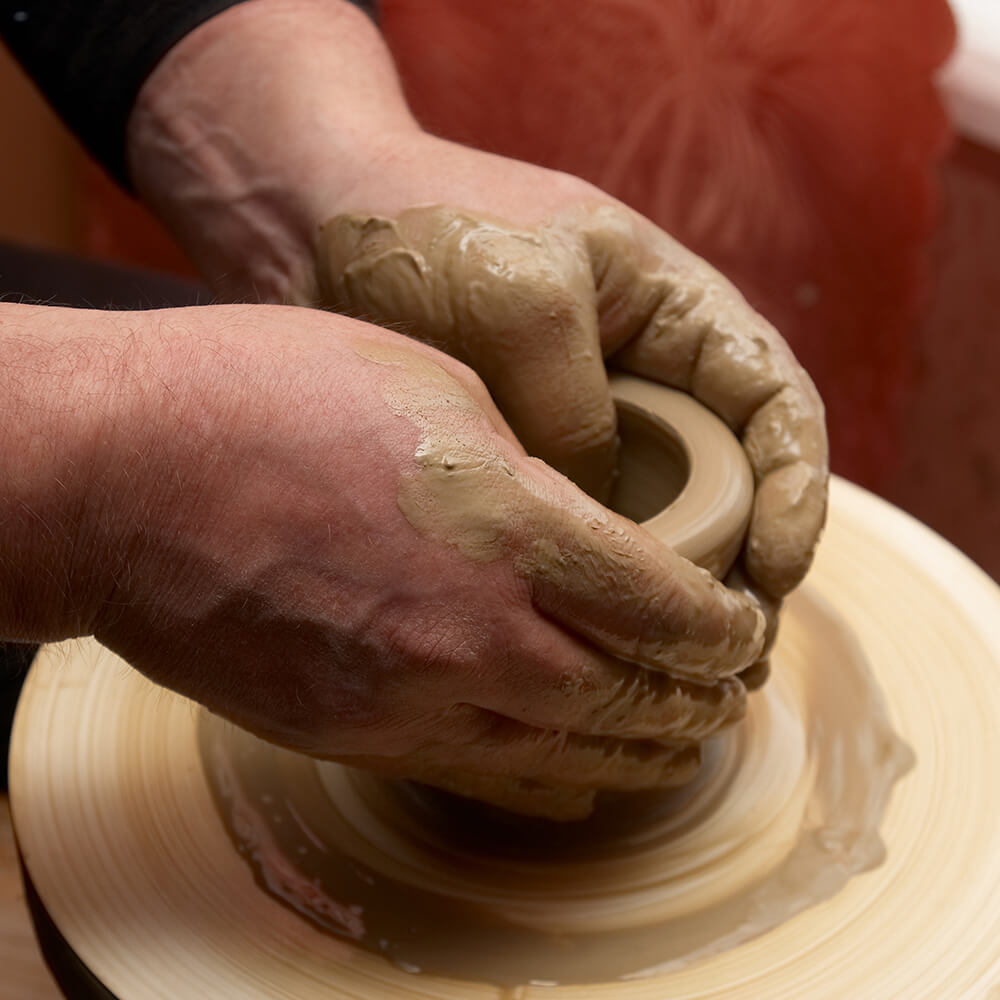 Two hands making a small pot on a pottery wheel