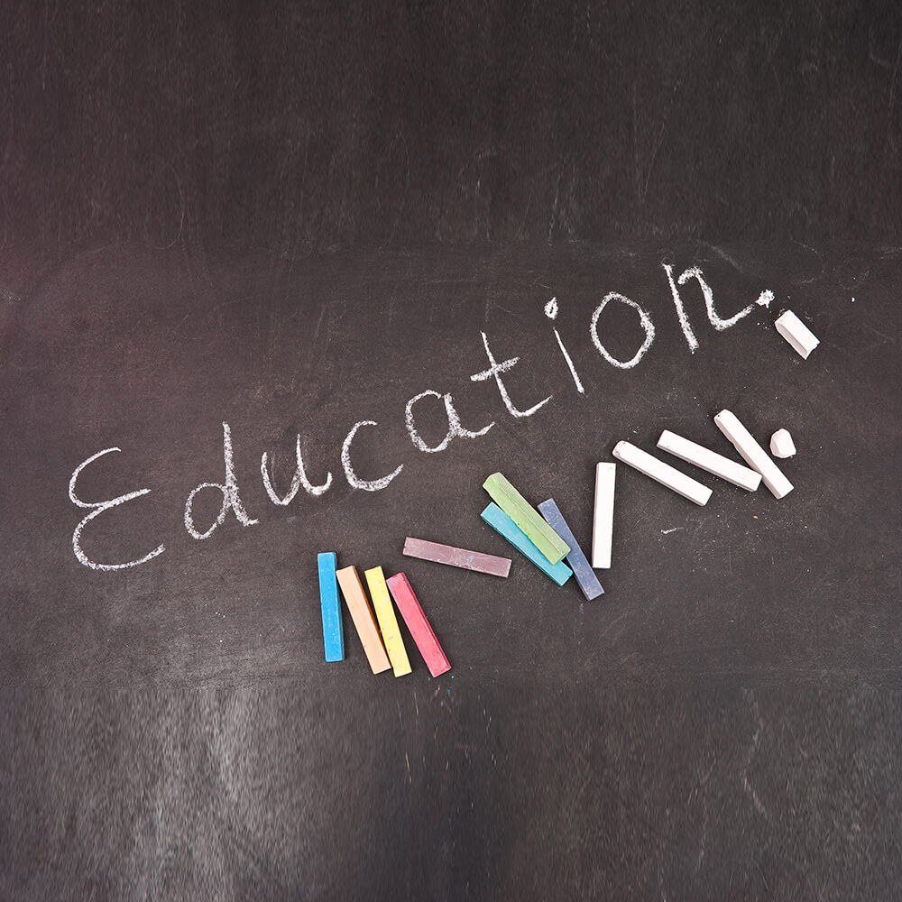 The word educatin written on a blackboard and various colors of chalk