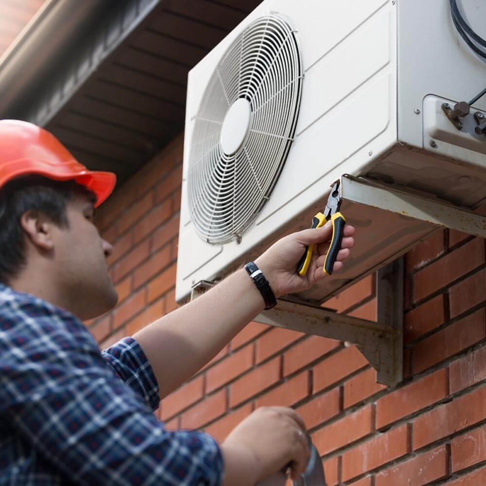 A man connecting an outdoor air conditioning unit