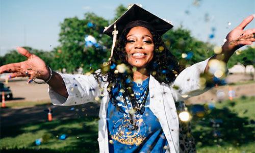 young black woman wearing a graduation cap throwing glitter