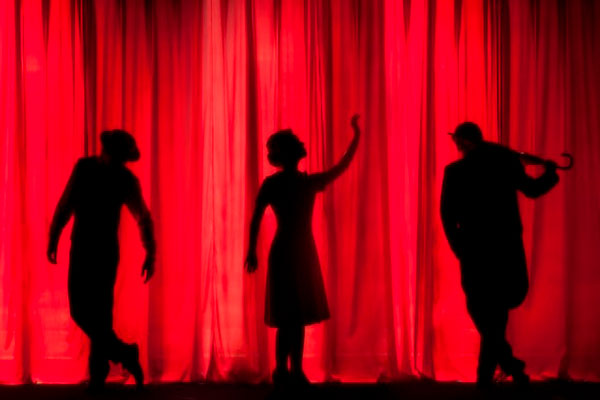 3 silhouettes on stage with a red curtain in the background