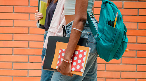 students walking with backpack and notebooks