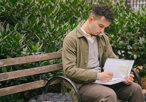 young male student sitting on a bench reading a textbook