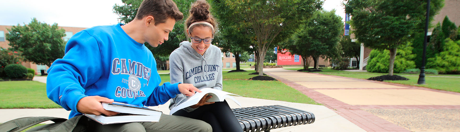 a male and female student sitting on a bench with school books