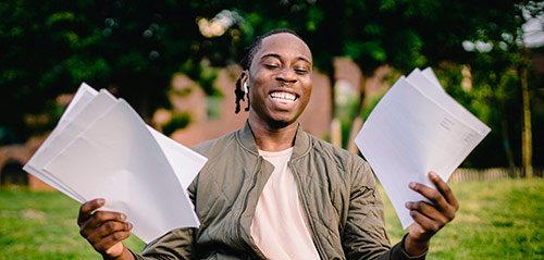 Young African American man holding papers and smiling