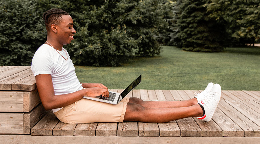 young black male student looking through transfer resources on laptop