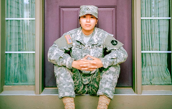 woman in us army uniform sitting in front of a door